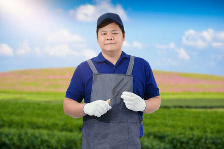 Male gardener hand holding shovel or garden tools and blurred background is flower garden