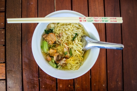 Pork noodle with chopstick and spoon on wood background thai food  photo