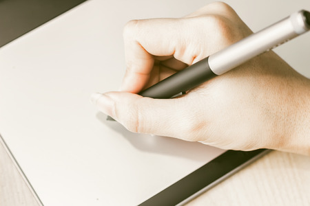 drawing up: Retro image of female hand of a designer drawing with the stylus on a grey graphics tablet