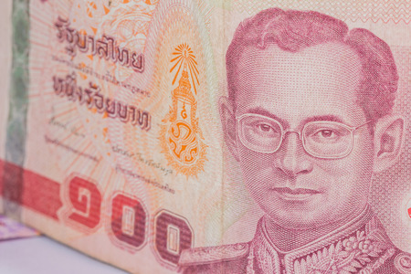 denomination: Close up of thailand currency, thai baht with the images of Thailand King. Denomination of 100 bahts.