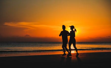 silueta hombre: joven pareja: hombre y mujer corren juntos en una puesta de sol en la costa del lago. Silueta.