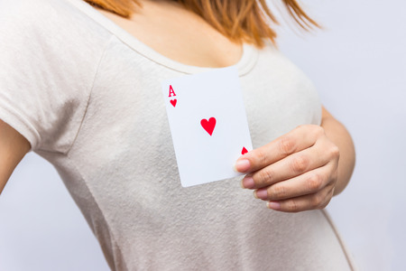 money risk: young woman holding in hand poker card with combination of Full House. in focus hand and poker card. Stock Photo