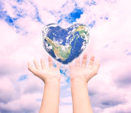 universal love: Mundo en forma de corazón con las mujeres más de la mano del hombre sobre fondo natural cian azul turquesa árbol borrosa y el cielo