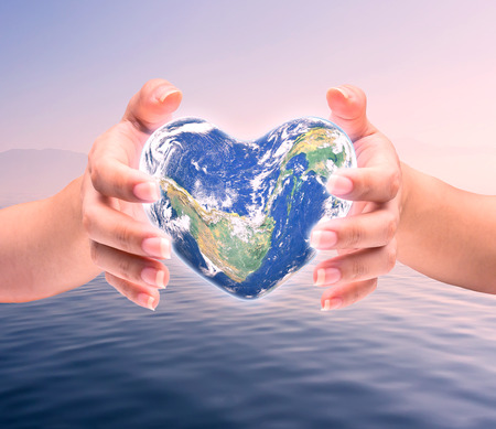 environment protection: World in heart shape with over women human hands on blurred natural background blue cyan turquoise tree and sky Stock Photo