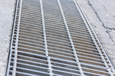 grate: Black and white close up of a sidewalk subway grate with shallow depth of field. Stock Photo