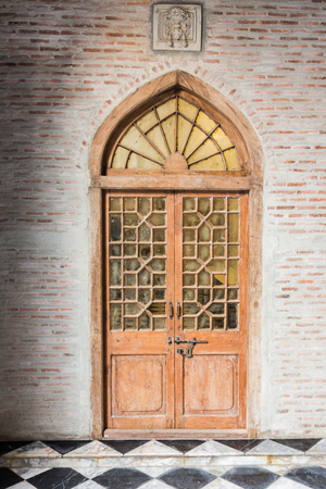 stoop: The wooden front door of a home with glass panels to each side and a brick porch. The glass is reflecting the homes opposite the door. Vertical shot.