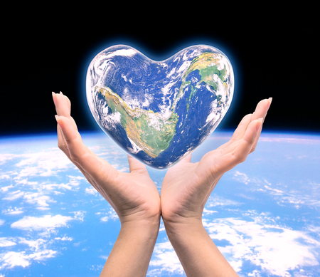 World in heart shape with over women human hands on blurred natural background: World Heart health day