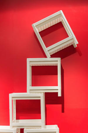 stackable: White Stackable chairs, red walls.