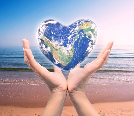 mapas conceptuales: World in heart shape with over women human hands on blurred natural background: World Heart health day,Element of this image furnished by NASA