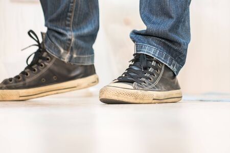 skinny jeans: A pair of vintage looking, athletic shoes and skinny jeans