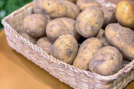 top view of new potatoes in a basket on a gray wooden background Stock Photo