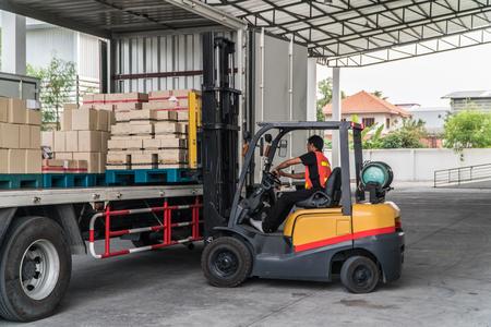 포크 리프트를 지게차로 트럭에 적재하는 작업자