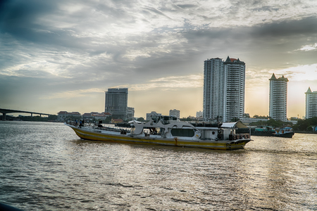 Bangkok, Thailand - August 5th 2017: Hotels, river Chao Praya and ferry station and ferry boat seen from bridge at station Saphan Taksin. On river are many small boats. Local ferry between two riversides is crossing river with many people on board. Editorial