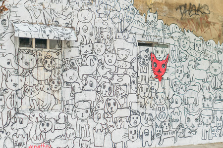 Wall of old vintage house with simple cat and dog graffiti.