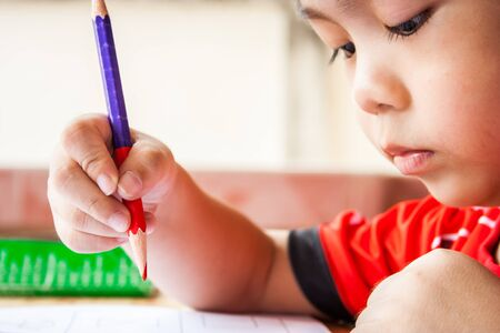 letter writing: Preschool children is painting with red color pencil.