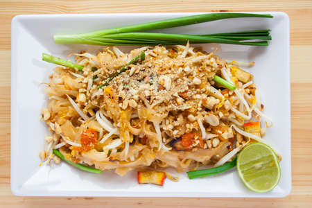 thai noodle: Thai noodle with lemon in white plate is on the wooden table.