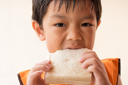 comiendo pan: El muchacho está comiendo el pan de molde. Foto de archivo