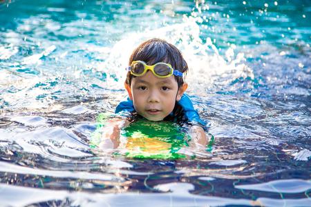 boy learn to swim in the swimming pool 写真素材