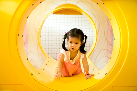 A little smile girl is crawling out of yellow tunnel at playground. Stock Photo