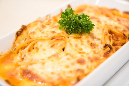 Spaghetti cheese baked in white bowl on the table.
