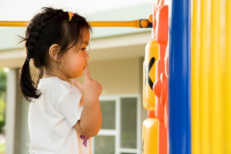 A little girl is playing in playground.