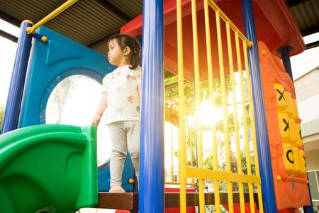 Una bambina sta giocando nel parco giochi. Archivio Fotografico - 87857114