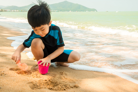 A boy in swimming suit is sitting on the beach and playing sand at the sea in the sunny day in summer. Stock Photo