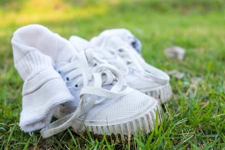 The dirty old canvas shoe was used as training shoe is on the grass at the garden.