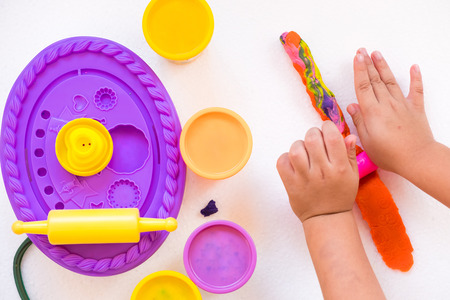 Children are molding colorful clay dough to various beautiful shape with imagination. Stock Photo