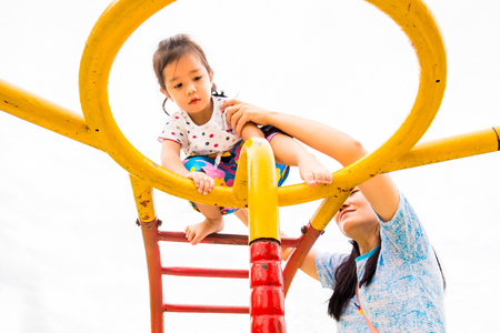 kids climbing up ladder with confident at playground for muscle training with take care from parents.
