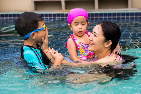 family spent time to swim in swimming pool. they enjoy playing together with laughing. 写真素材