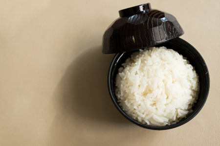 The cooked jasmine rice is rich in carbohydrates in a black wooden cup is placed on the table and ready to served as breakfast.