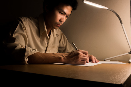 A busy business man is sitting on the chair for working overtime at office at night. He use a led lamp for lighting his desk for writing and typing laptop for research information. 写真素材