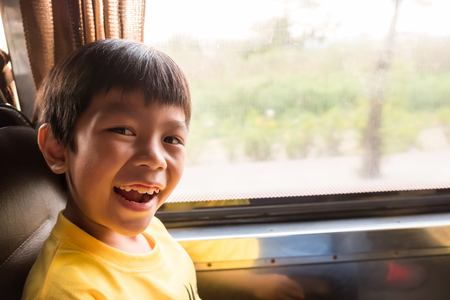 a laughing boy is traveling to the city by the metropolis bus in the morning. he enjoy with this transportation, traffic not jam and good weather
