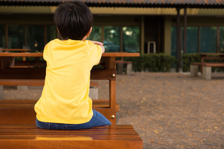 a little boy sitting on the wooden table with lonely feeling at school. he waiting for his parents after school 写真素材