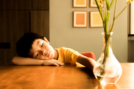 a little boy sitting on the wooden table under the sunlight in the evening with lonely feeling at home. he has no friends to play with him