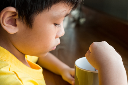 a little boy sitting at the wooden table by the window at home to drink a cup of hot chocolate. he hold the cup in his left hand and mixed hot chocolate with cream with a teaspoon in his right hand