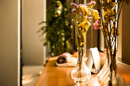 colorful fresh flowers is in the vase under the sunlight by the window. it's decoration on the breakfast wooden counter with chocolate, strawberry doughnut. 写真素材