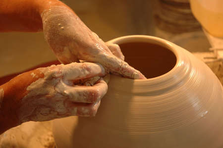 ceramic artist working at pottery studio creating new clay piece