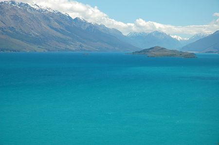 Vibrant turquoise colour lake surrounded by snow mountain peaks. Lake Whakatipu, Queenstown, New Zealand. 版權商用圖片