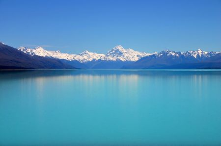 Beautiful mountain turquoise color lake, blue sky and snow peaks reflecting in the water. Untouched nature. Mount Cook National Park, New Zealand photo