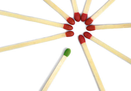 differently: Red matches in a circle and green one coming in. Concept - newcomers, fresh ideas, think different. White background, isolated.