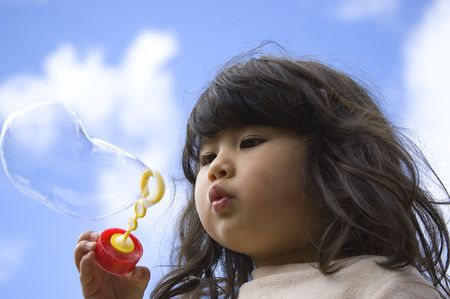 Cute little girl making bubbles. Blue sky on the background.