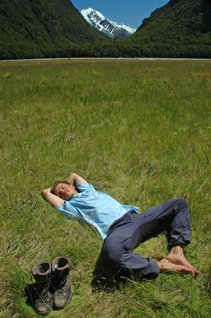 Barefeet young man in blue top resting on green grass surrounded by snowy mountains and wild forest after trekking. His boots are aside. 版權商用圖片