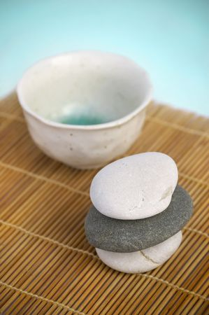 Tranquil Zen style scene. Ceramic cup and pebbles on bamboo mat 版權商用圖片