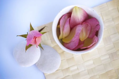 Spa tranquility. Rose bud and petals with pebbles and cup on a cane mat. 版權商用圖片