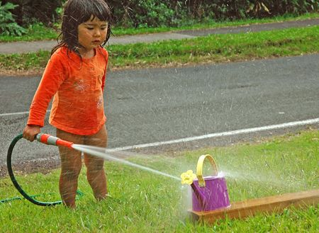 sprinkling: Cute little girl in orange top holding a water hose and sprinkling water over green grass and a watering-pot in summer day Stock Photo