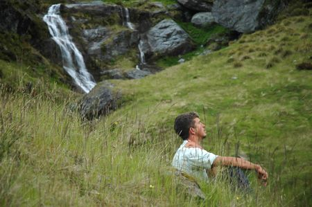 A young man in blue t-shirt surrounded by waterfalls sitting in high grass and enjoying the nature