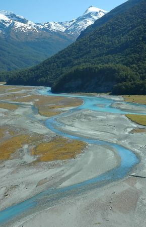 Turquoise winding river, green forest, snowy mountains and blue sky landscape. Dart river valley, Queenstown, New Zealand.  版權商用圖片