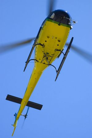 Yellow helicopter in blue sky closeup bottom view photo